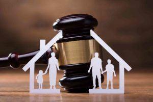 Richterhammer hinter getrenntem Haus und getrennter Familie aus Papier