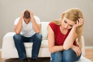 Ehepaar sitzt mit verzweifelter Miene auf einem Sofa