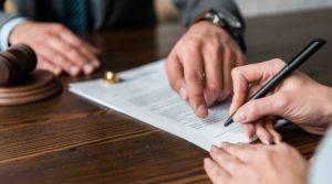 Richterhammer Anwaltshände die auf Scheidungspapiere zeigen Eheringe Frau die unterzeichnet