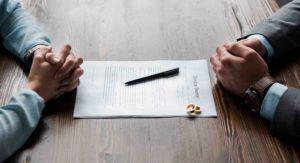 Frauen- und Männerhände dazwischen Scheidungspapiere und Eheringe
