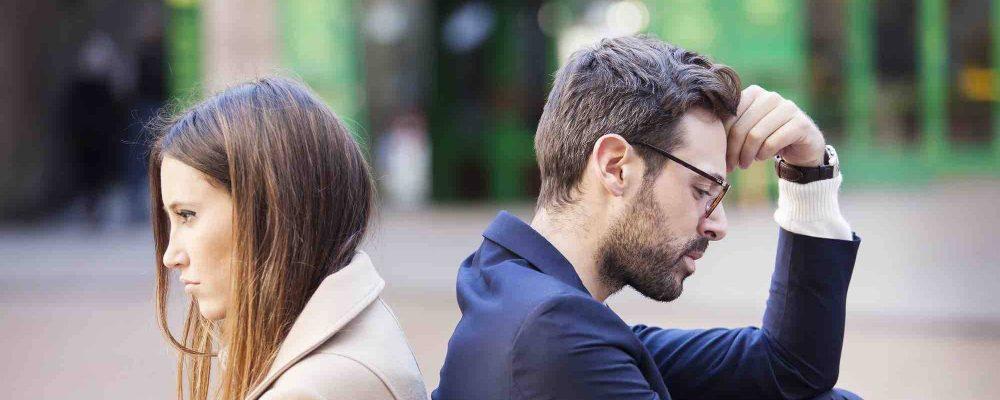Ehepaar sitzt mit Rücken zueinander nach einer Scheidung
