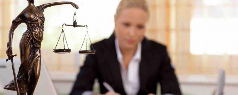 Junge Anwältin sitzt am Schreibtisch