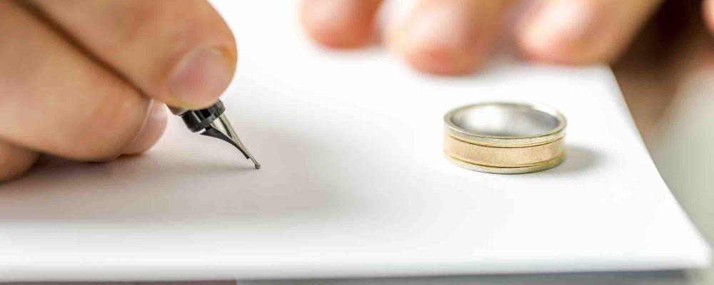 Ehering liegt auf Scheidungsvertrag