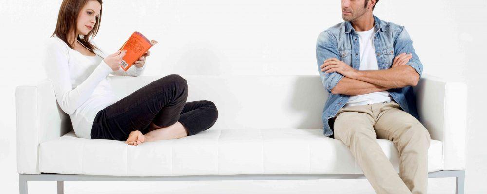 Paar sitzt getrennt auf einer Couch