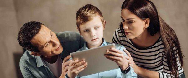 Vater und Mutter hocken hinter Kind mit Tablet in der Hand