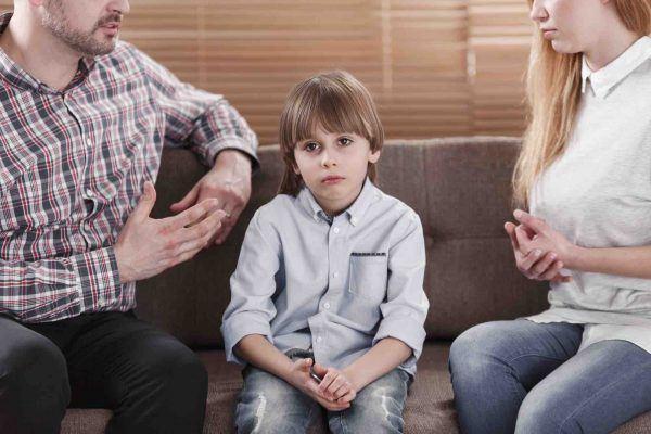 Kind sitzt zwischen Mutter und Vater