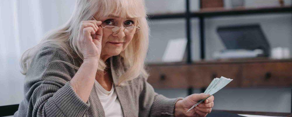 Ältere Frau zählt Geld am Tisch