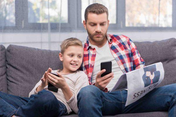 Vater und Sohn spielen am Smartphone