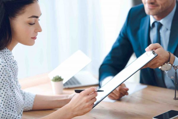 Frau unterzeichnet Vereinbarung beim Scheidungsanwalt