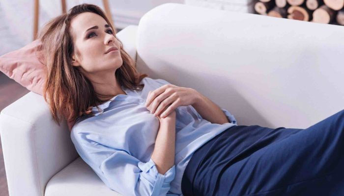 Frau liegt nachdenklich am Sofa